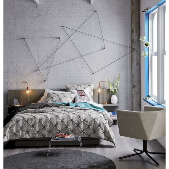 Creative grey accented concrete wall decorated with triangular wall art