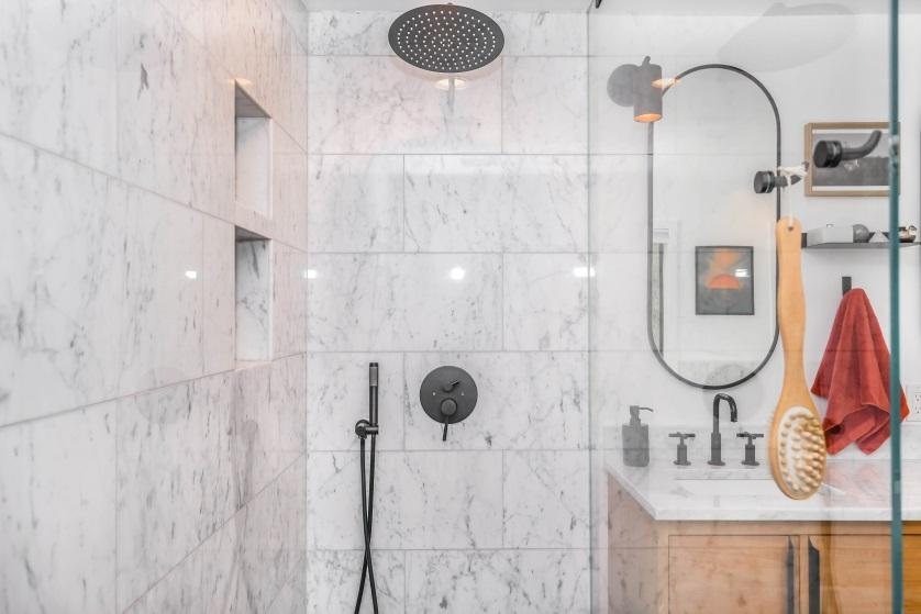 Black showerhead installed on the wall instead of the ceiling